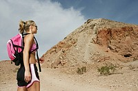 Woman wearing a backpack, looking at a large hill