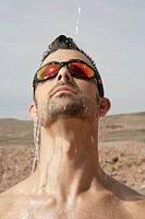 Close-up of a Caucasian man with water pouring down his face
