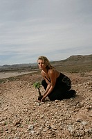 Woman holding a sapling in the desert