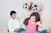 Close-up of a girl holding a teddy bear and her father sitting behind her