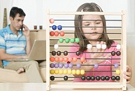 Girl playing with an abacus with her father talking on a mobile phone in the background