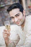 Portrait of a young man holding a champagne flute and smiling