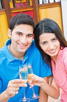 Portrait of a young couple toasting with champagne flutes and smiling