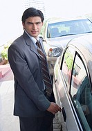 Portrait of a businessman unlocking a car