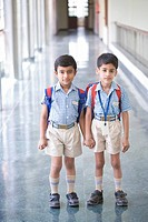 Portrait of two boys standing in a corridor with holding hands of each other