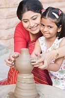 Girl with her teacher in a pottery class