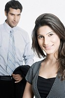 Portrait of a young woman smiling with a businessman standing behind her