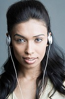 Portrait of a young woman listening to headphones and smiling