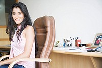 Side profile of a businesswoman sitting on an office chair and smiling