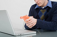 A man pointing a toy gun at a laptop