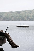 A woman with a laptop sat on a jetty
