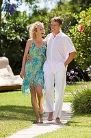 A mature couple walking through a garden