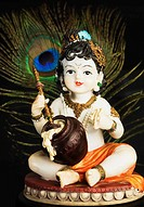 Close-up of a figurine of God Krishna with a peacock feather