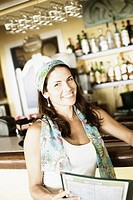 Portrait of a mid adult woman at a bar counter and smiling