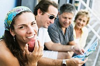 Portrait of a mid adult woman eating an apple with her friends sitting beside her