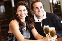 Mid adult couple sitting in a bar and holding beer in stem glasses