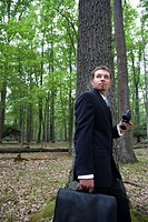 Portrait of young businessman in forest with binoculars