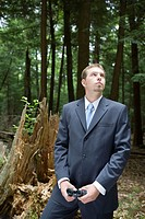 Portrait of young businessman standing in forest