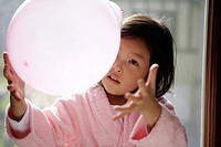 Girl in a bathrobe playing with a balloon