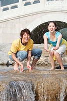 Young couple splashing water, smiling, portrait
