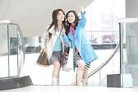 Young women at staircase in shopping mall