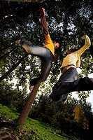 Young couple jumping, low angle