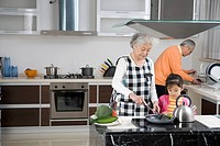 Senior couple and granddaughter cooking in kitchen