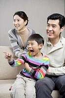 Family sitting on sofa and son shouting