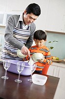 Father teaching son how to wash dishes