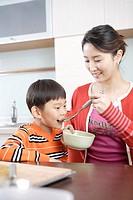 Mother feeding boy in kitchen