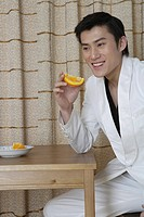 Man holding sweet lime slice, smiling