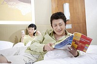 Woman using mobile phone while man reading a magazine