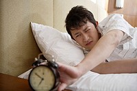 Young man looking at alarm clock