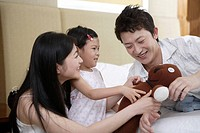 Family playing with toy and smiling