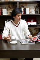 Young man with coffee cup and magazine