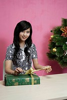 Young woman opening gift, smiling, portrait