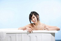 Portrait of a woman sitting in bathtub and holding glass of water