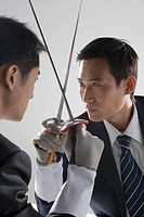 Two young businessmen sword fighting