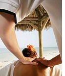 Young woman getting back massage at beach