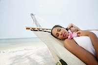 Young couple relaxing in hammock on beach