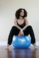Woman sitting on a exercise ball smiling