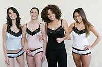 Four women in lingerie arm in arm, looking at camera