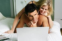 Young happy couple relaxing in bed with laptop (thumbnail)