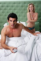 Man watching TV in bed with topless woman in background