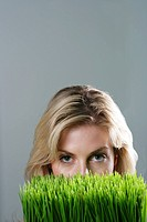 Woman peeking over grass blades