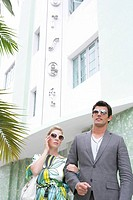 Fashionable couple waiting outside hotel