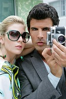Fashionable couple with camera