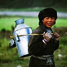 Tibetan teenage girl carrying steel pot with rope