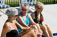 Senior women sitting at edge of swimming pool