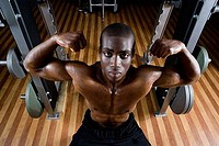 Portrait of a young man flexing muscles in the gym